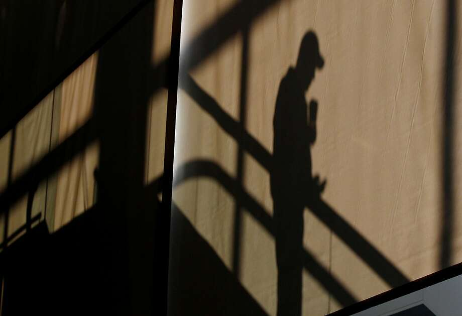 A man is silhouetted against a sun screen by window light as he descends an escalator in terminal E at Logan International Airport in Boston, Monday, Jan. 7, 2013. Photo: Stephan Savoia, Associated Press