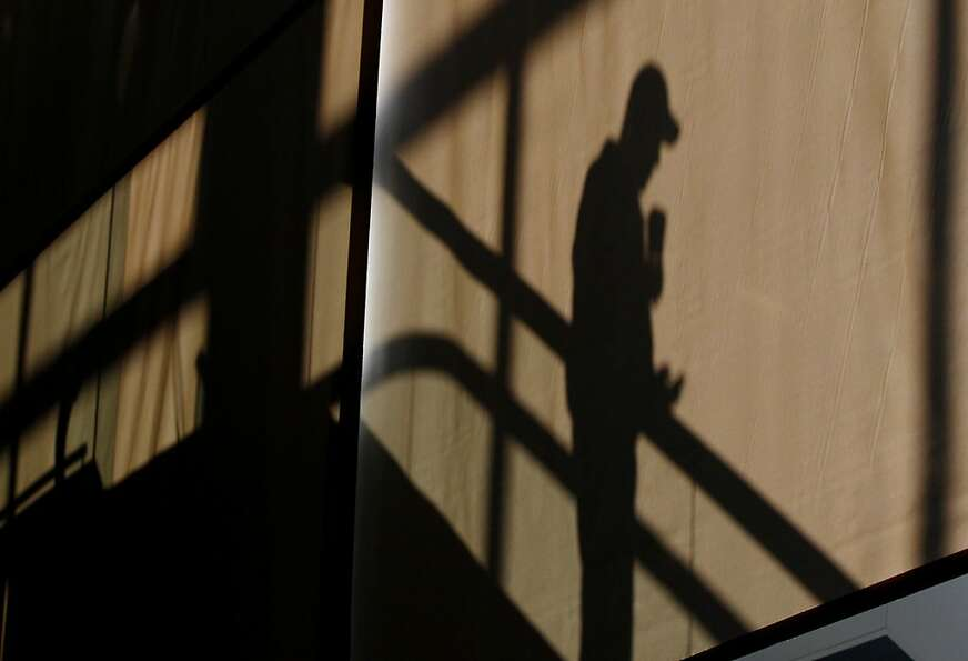 A man is silhouetted against a sun screen by window light as he descends an escalator in terminal E