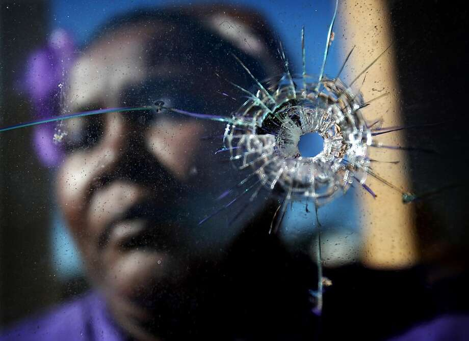 Emma Jackson holds up her bedroom window, Monday, Jan. 7, 2013 outside her Montgomery Plaza apartment in South Memphis, Tn. near South Parkway and Florida. Jackson said on two occasions in 2012 gunmen shot into her home targeting her 20-year-old son who no longer lives there. The first incident in May 2012 a shot when through her opened front door. On the second incident December 12, 2012 shots were fired through her bedroom window in the front of the unit and the kitchen window in the back. Photo: Mike Brown, Associated Press