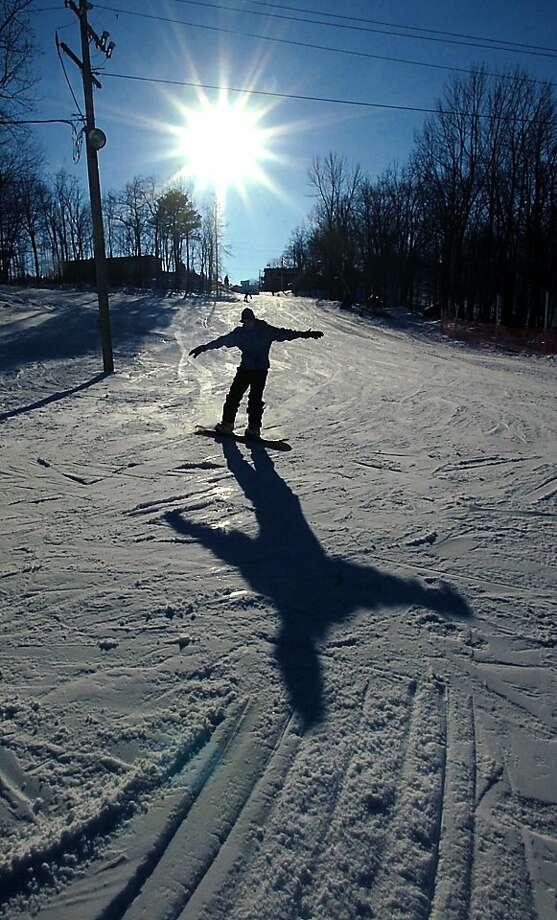 A snowboarder glides down a ski path at Sno Mountain on Monday, Jan. 7, 2013 in Scranton, Pa. Photo: Butch Comegys, Associated Press