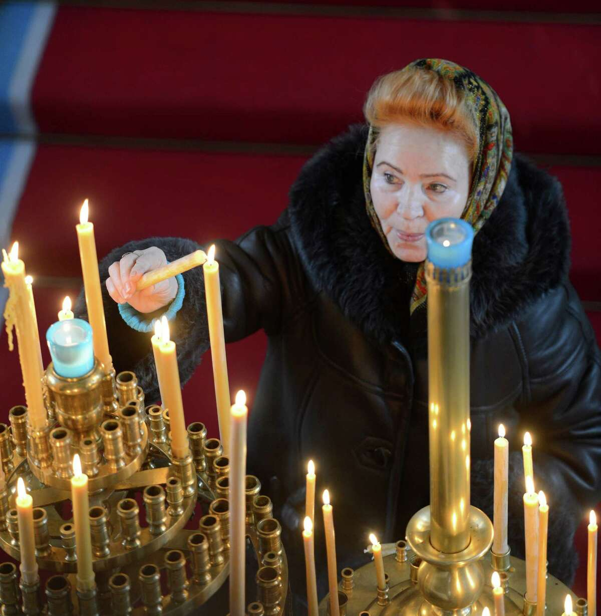 A parishioner lights candles before the Christmas Day celebration at the Nativity of the Mother of God Russian Orthodox Church Monday morning, Jan. 7, 2013. in Colonie, N.Y. The Russian Orthodox Church uses the
