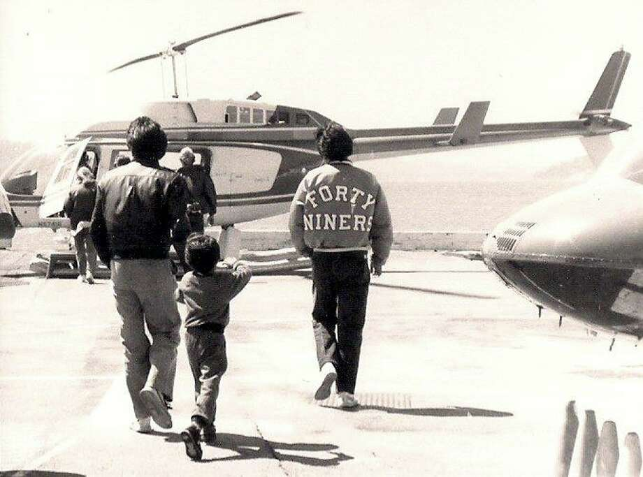 Troy is wearing his 49ers jacket in 1986, next to his brother and his dad, at Fisherman's Wharf about to take a helicopter ride for Father's Day. He writes: It was kinda mandatory to have a gold 9er jacket back in the days. I never bought one, but I always seemed to have one. I traded an Adidas Jacket for a friends 9ers for a few days. They lost mine, so I kept theirs. I came up on one at a school dance.
