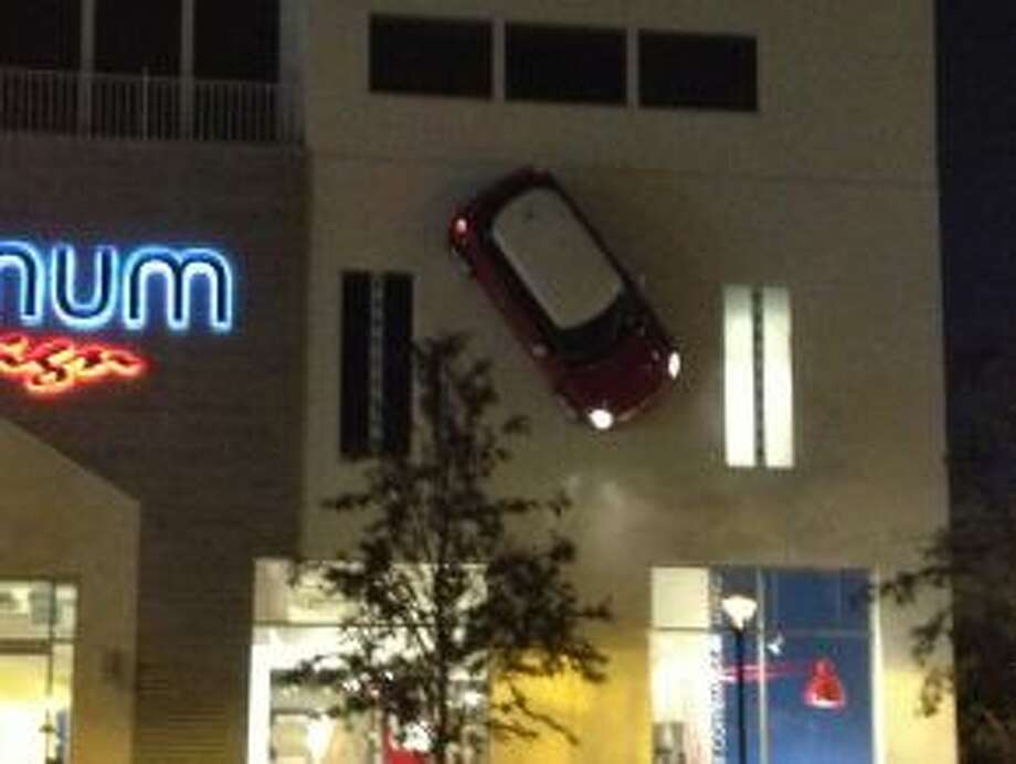 A fake Mini Cooper sits on the side of a building housing the store Internum. Photo: Dan X. McGraw
