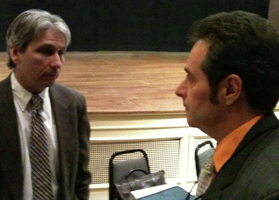 Michael A. Caron, left, director of the state's Public Utilities Regulatory Authority, talks with Frank Cirillo, who represents CL&P's line workers, during a break in Monday night's public hearing in Town Hall.  Westport CT 1/7/13 Photo: Andrew Brophy / Westport News contributed