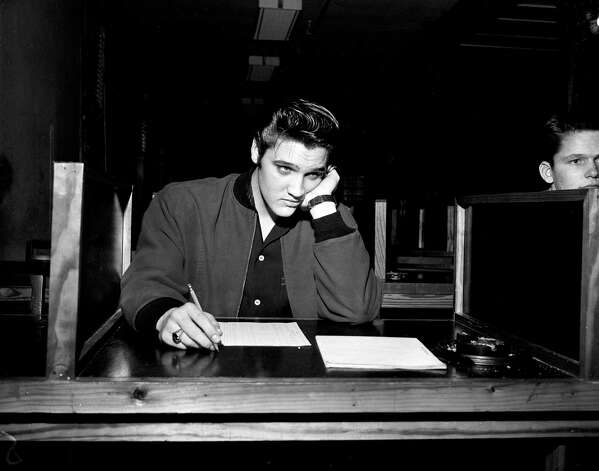 Singer Elvis Presley, 21, takes his pre-induction written examination as he is processed for the U.S. Army in Memphis, Tenn., Jan. 4, 1957.  (AP Photo)