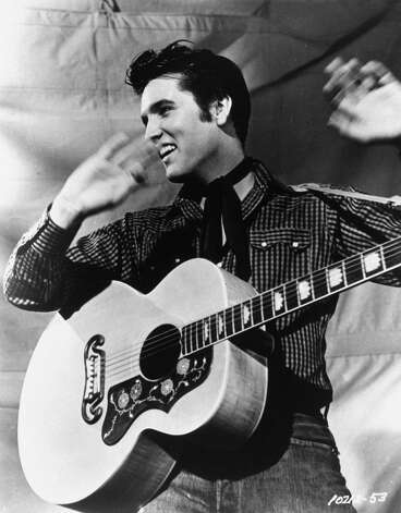 "Elvis Presley is shown with his Gibson J-200 guitar in a 1957 MGM studio publicity photo.  Born in Tupelo, Miss., Elvis was an immediate sensation in the mid-1950s with his blend of blues rock and rockabilly.  Because of  his stage gyrations,  television producers initially refused to show him below the waist on screen.  Critics called him ""Elvis the Pelvis,"" but his fans called him the ""King of Rock 'n' Roll.""  The Elvis empire grew with live performances, records, films and a grand estate in Memphis,Tenn.,  known worldwide as Graceland.  Elvis died at Graceland on Aug. 16, 1977.  He was 42.  (AP Photo) Photo: Anonymous, HO"