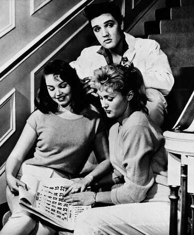 Elvis Presley, poses with his house guests, Kathy Gabriel, left, and Hanneri Melcher, Dec. 27, 1957, Memphis, Tn. Miss Melcher is shown pointing to March 20th on the calendar. (AP Photo)