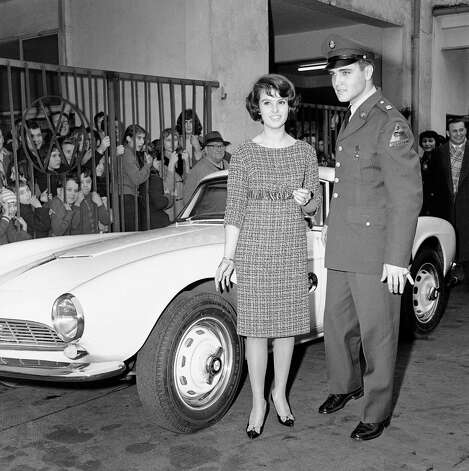 Pfc. Elvis Presley shown with Ursula Siebert in front of German sports car at Frankfurt, West Germany, auto agency on Dec. 20, 1958. Curious youngsters crowd railing at left for a look at Elvis who is stationed on base at nearby Friedberg. The car, a BMW 507, made by the Bavarian Motor Co., is a sleek two-seater, painted white on the outside and upholstered with white and black leather inside. Dealer said he had sold the car, a used demonstration model, to Elvis for $3,750. When new, it could cost about $7,500. (AP Photo/Kurt Strumpf) Photo: Kurt Strumpf, STF