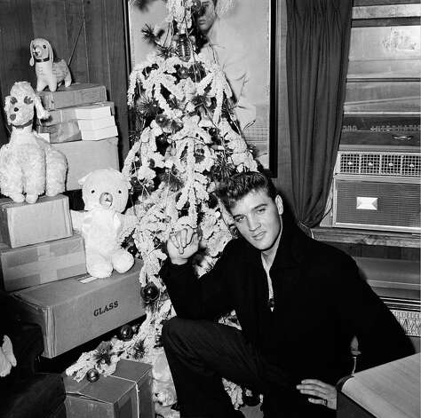 Elvis Presley poses by a Christmas tree at his home in Memphis, Tenn., in 1960.  (AP Photo)