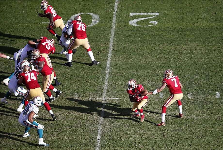Colin Kaepernick (right), handing off to LaMichael James in the 49ers' win over Miami, is 5-2 as a starter, but opponents - and fans - still don't know him. Photo: Stephen Lam, Special To The Chronicle