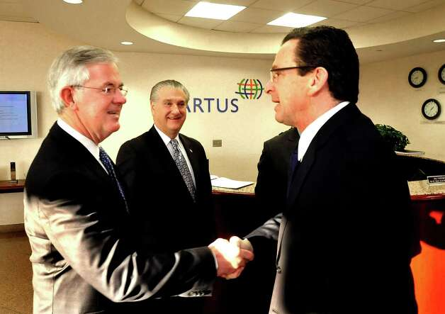Kevin Kelleher, president and CEO of Cartus, left, and Joe Walkovich, a Greater Danbury Chamber of Commerce member, greet Connecticut Gov. Dannel P. Malloy, right, who was the keynote speaker at a chamber breakfast held at Cartus Tuesday, Jan. 8, 2012. Photo: Michael Duffy