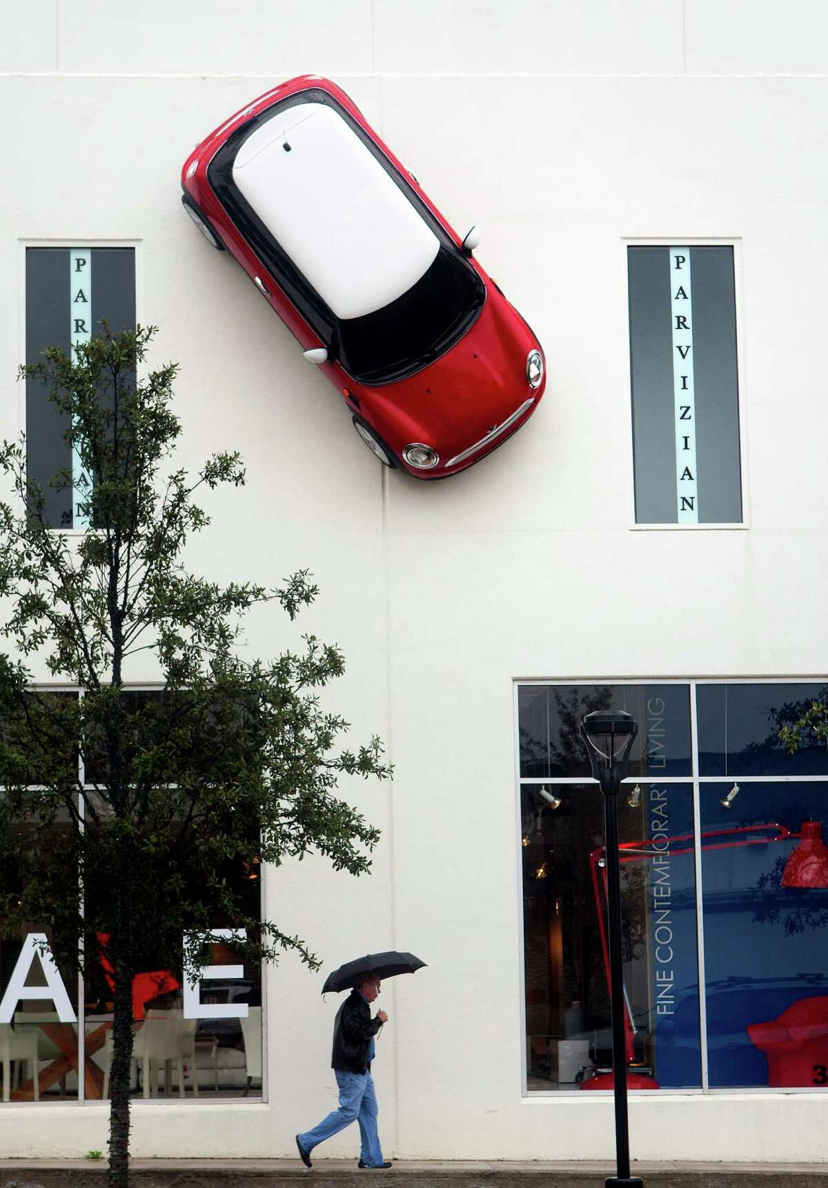 A man walks beneath a Mini Cooper hanging from the front of internum, a design store, on Kirby Drive, Tuesday, Jan. 8, 2013, in Houston. The City of Houston Code Enforcement hung a notice on the door of the business telling them to take the car down immediately.