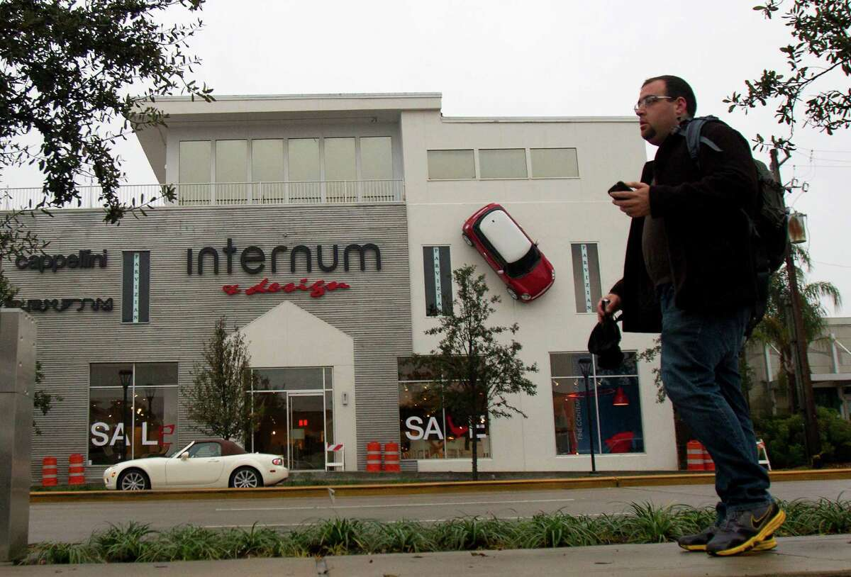 Chris Martinez by a Mini Cooper hanging from the front of internum, a design store, on Kirby Drive, Tuesday, Jan. 8, 2013, in Houston. The City of Houston Code Enforcement hung a notice on the door of the business telling them to take the car down immediately.