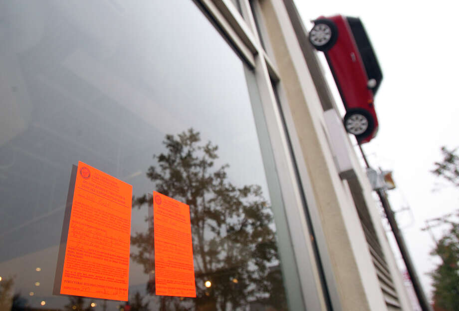 A notice from the City of Houston Code Enforcement is seen on the front door of internum, a design store, on Kirby Drive, Tuesday, Jan. 8, 2013, in Houston. The City of Houston Code Enforcement hung a notice on the door of the business telling them to take the car down immediately. Photo: Cody Duty, Houston Chronicle / © 2012 Houston Chronicle