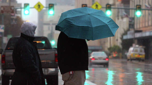 Pedestrians wait in the rain Tuesday January 8, 2013 to cross East Commerce street in downtown San Antonio. Showers and thunderstorms are expected to continue through the day with high temperatures reaching the 50s. Wednesday's forecast calls for a 90 percent chance of rain. Photo: JOHN DAVENPORT, San Antonio Express-News / ©San Antonio Express-News/Photo Can Be Sold to the Public