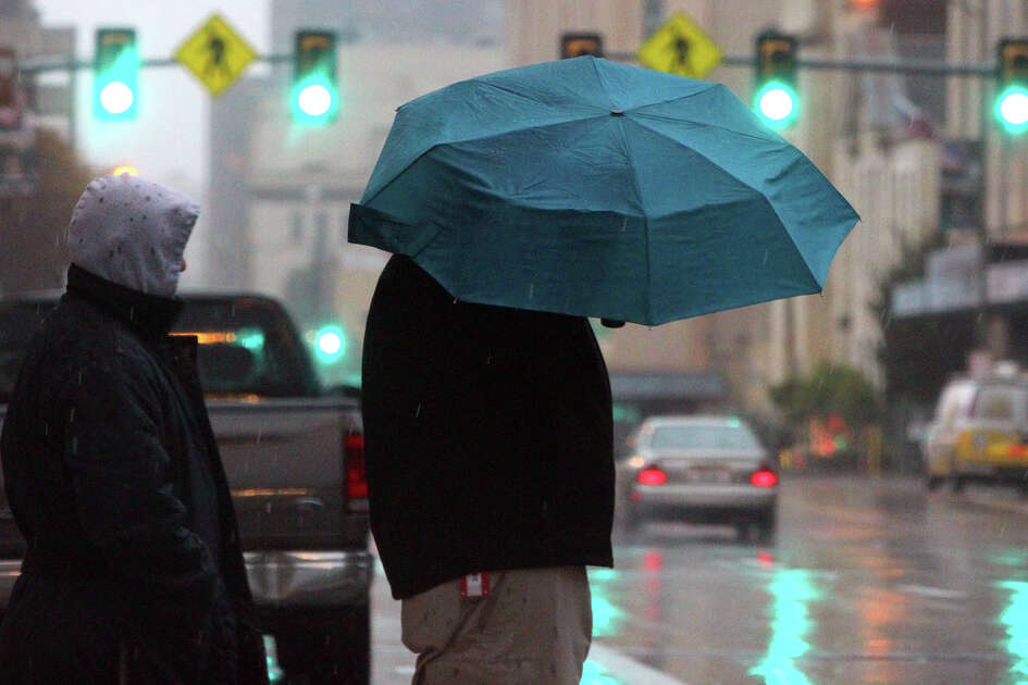 Pedestrians wait in the rain Tuesday January 8, 2013 to cross East Commerce street in downtown San Antonio. Showers and thunderstorms are expected to continue through the day with high temperatures reaching the 50s. Wednesday's forecast calls for a 90 percent chance of rain.