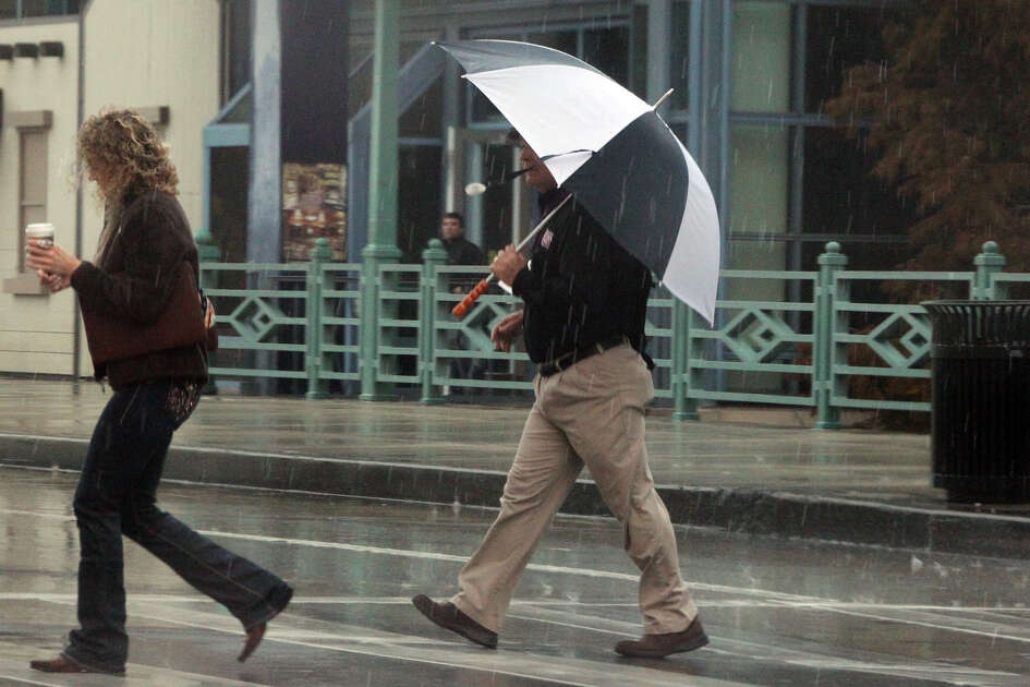 Pedestrians scurry through the rain Tuesday January 8, 2013 on East Commerce street in downtown San Antonio. Showers and thunderstorms are expected to continue through the day with high temperatures reaching the 50s. Wednesday's forecast calls for a 90 percent chance of rain.