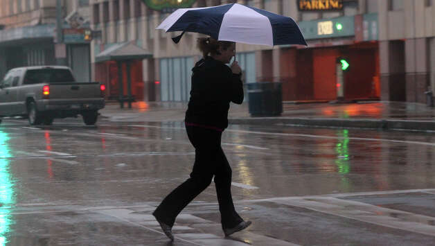 A pedestrian scurries through the rain Tuesday January 8, 2013 on East Commerce street in downtown San Antonio. Showers and thunderstorms are expected to continue through the day with high temperatures reaching the 50s. Wednesday's forecast calls for a 90 percent chance of rain. Photo: JOHN DAVENPORT, San Antonio Express-News / ©San Antonio Express-News/Photo Can Be Sold to the Public
