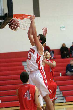 Judson's David Wacker (33) dunks between two Lee Volunteer defenders during the Rockets' 85-55 win Friday over the Vols. Photo: Greg Bell / For The NE Herald