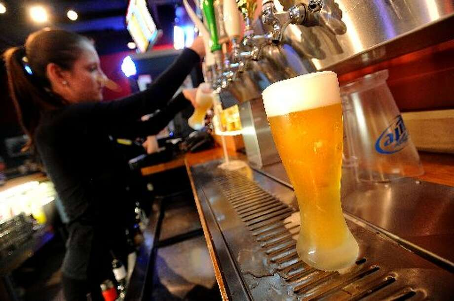 Elyse McGinnis pours a beer for thirsty patrons at Buffalo Wild Wings in Beaumont. Guiseppe Barranco/cat5