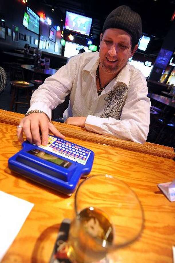 Michael Brooks catches up on a few rounds of Buzz Time Trivia at Buffalo Wild Wings in Beaumont. Guiseppe Barranco/cat5