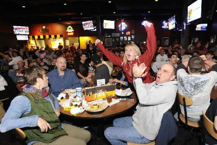 At Buffalo Wild Wings, Alabama fans, Dawn Dexter, center, and Stan Larson, right, react in a sea of Longhorn fans as the Crimson Tide takes on Texas during the first half of their national championship game in 2010. Valentino Mauricio/cat5