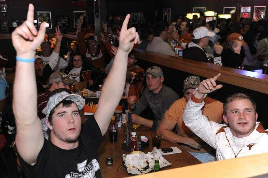 At Buffalo Wild Wings on Dowlen Rd., University of Texas graduates Jacob Hannna, left, and Chase Rayburn, right, react as the Longhorns score in the first quarter against the Alabama Crimson Tide during their national championship game in 2010. Valentino Mauricio/cat5