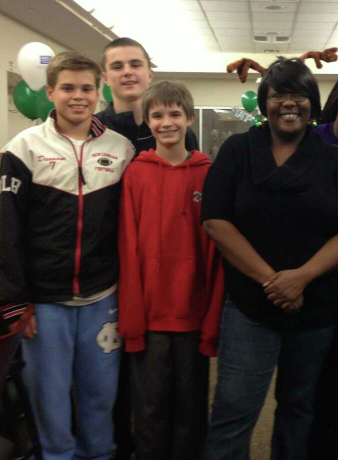 A holiday party for  Breakthrough Options for Families was made a little brighter by the donations of three Saxe Middle School eighth-graders Troy Dunnam, Ryan OíConnell and Josh Kloud, who came to the aid of Akisha Cassermere, the founder of the organization. Photo: Contributed