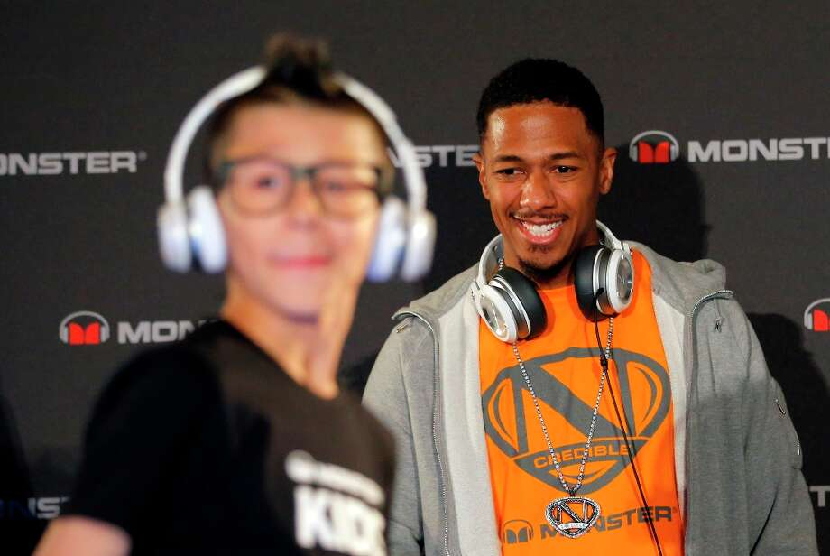 Recording artist Nick Cannon looks at a model wearing a new headphone by Monster during a new conference at the International Consumer Electronics Show in Las Vegas, Monday, Jan. 7, 2013. The 2013 International CES gadget show, the biggest trade show in the Americas, is taking place in Las Vegas this week. (AP Photo/Jae C. Hong) Photo: Jae C. Hong, Associated Press / AP