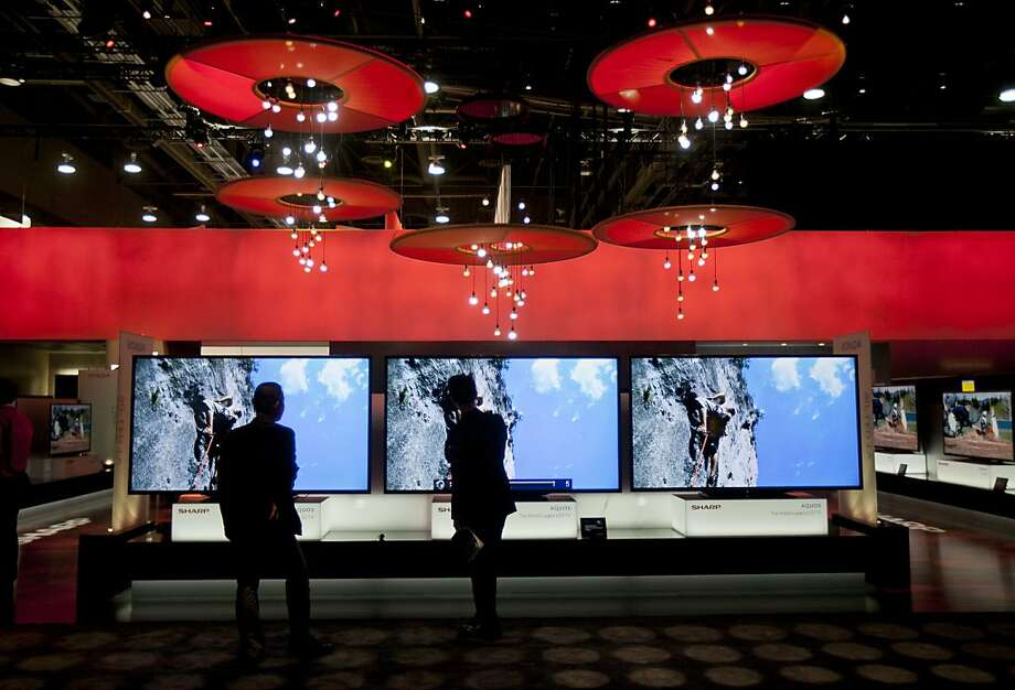 Attendees look at Sharp Corp. 90-inch televisions during the 2013 Consumer Electronics Show in Las Vegas, Nevada, U.S., on Tuesday, Jan. 8, 2013. Photo: Andrew Harrer, Bloomberg
