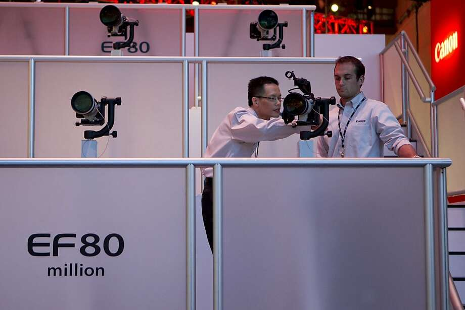 Canon Corp. representatives look at cameras during the 2013 Consumer Electronics Show in Las Vegas, Nevada, U.S., on Tuesday, Jan. 8, 2013. Photo: Andrew Harrer, Bloomberg