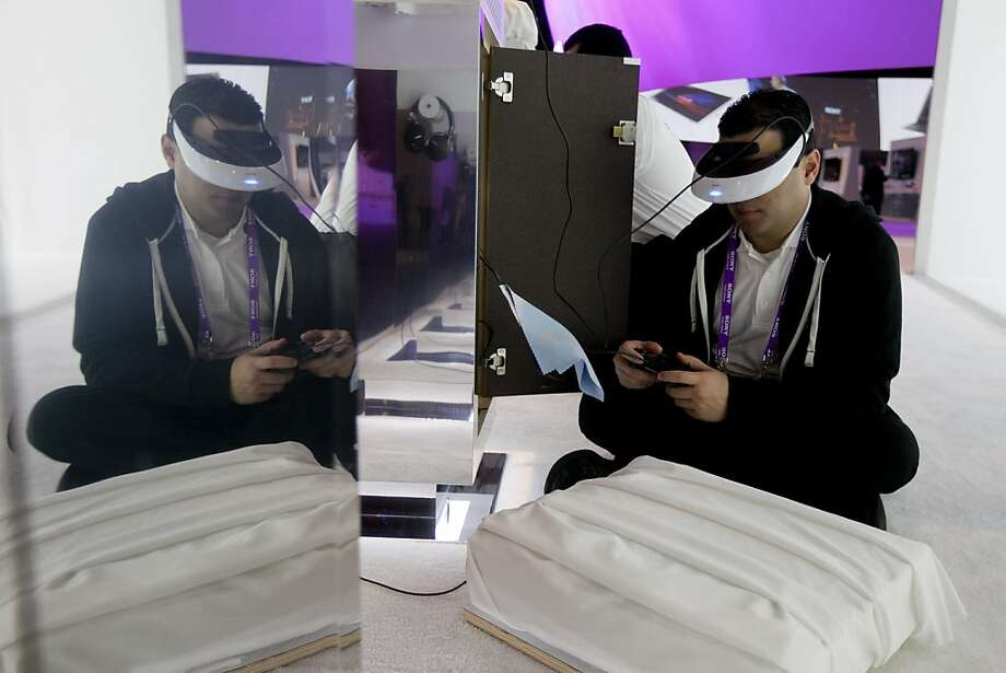Andrey Pinero sets up a Sony Corp. Personal 3D Viewer headset during the 2013 Consumer Electronics Show in Las Vegas, Nevada, U.S., on Tuesday, Jan. 8, 2013. The 2013 CES trade show, which runs until Jan. 11, is the world's largest annual innovation event that offers an array of entrepreneur focused exhibits, events and conference sessions for technology entrepreneurs. Photo: Andrew Harrer, Bloomberg