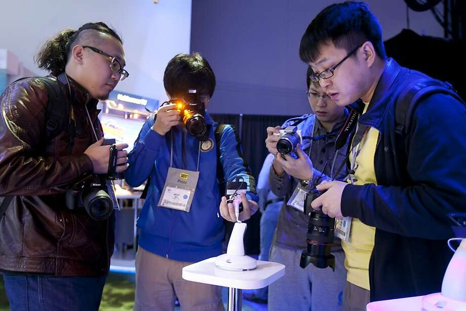Attendees take photographs of a reference design smartphone intended for emerging markets at the Intel Corp. booth during the 2013 Consumer Electronics Show in Las Vegas, Nevada, U.S., on Tuesday, Jan. 8, 2013. Photo: Andrew Harrer, Bloomberg