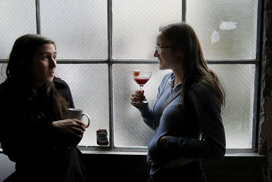 Drinking buddies: Asta Karalis (right) and Zoe Serrigno sip their beverages at the opening. Photo: Brant Ward, The Chronicle