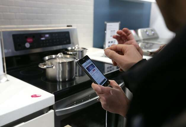 People try out the LG Smart Oven, which is controlled by a cell phone, on display at the show. Photo: Justin Sullivan, Getty Images