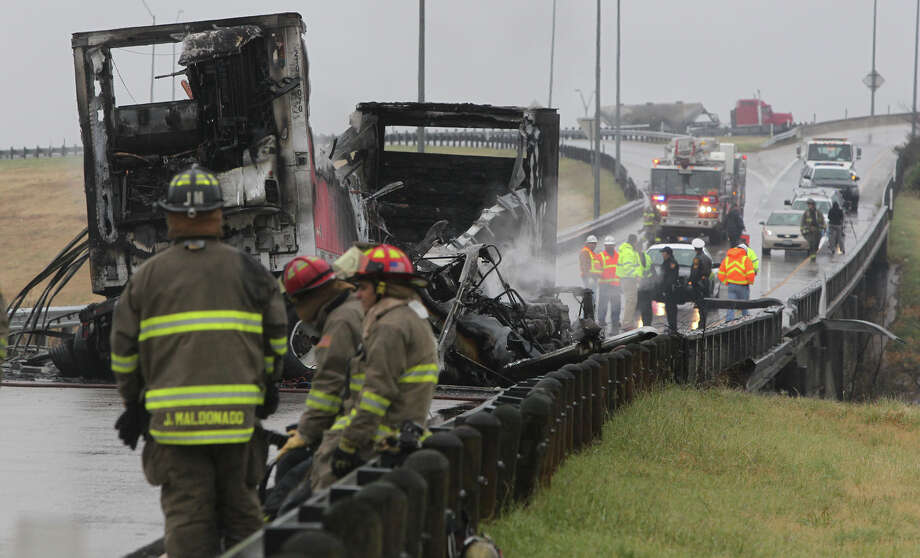 San Antonio police, fire and other personnel stand by the scene of a truck Tuesday January 8, 2013  that caught on fire after sideswiping a guardrail on a highway ramp connecting Loop 410 south to IH-37 south of downtown San Antonio. According to San Antonio police sergeant Donald Mize the truck was empty and the driver was not injured. Photo: JOHN DAVENPORT, San Antonio Express-News / © San Antonio Express-News