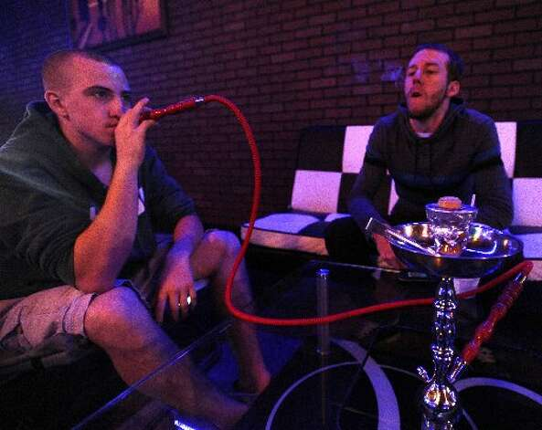 Micah Menard, left, and Josh Tindel, right, smoke hooka at The Arabian Nights Hookah and Oxygen Bar. Randy Edwards/cat5
