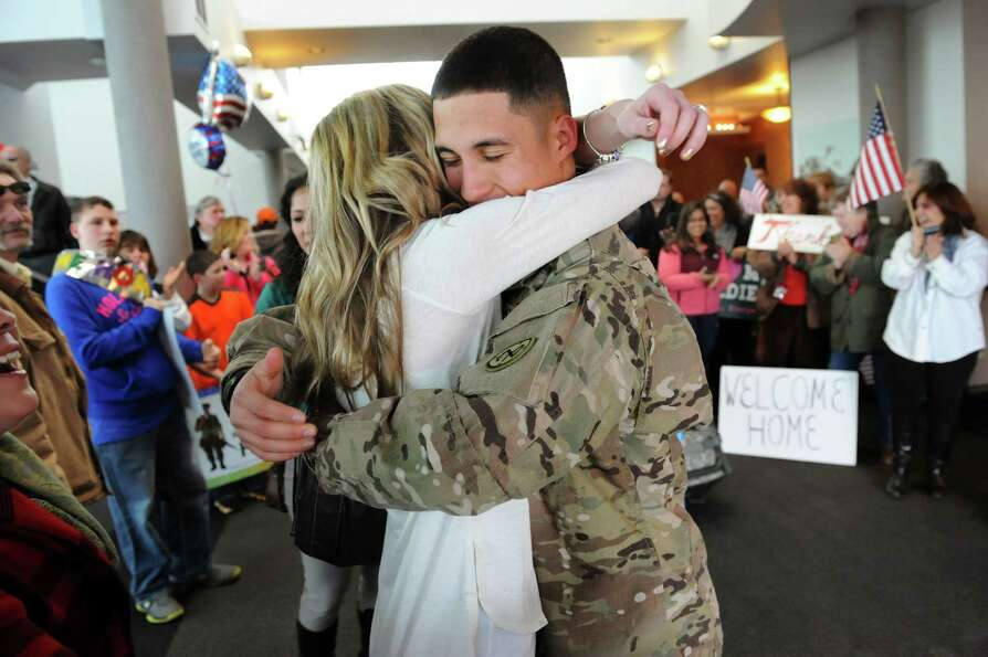 Sgt. Michael Mora of Albany, right, embraces his girlfriend, Allie Quivey, when he arrives home on T