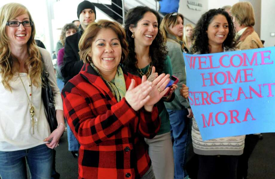 Loved ones of Sgt. Michael Mora of Albany, including his girlfriend Allie Quivey, left, and his mother Rosa Lugo, center, cheer for troops as they wait for Mora's arrival on Tuesday, Jan. 8, 2013, at Albany International Airport in Colonie, N.Y. Troops from the 27th Infantry Brigade reunite with family and friends following their deployment to Kuwait in support of Operation Enduring Freedom. (Cindy Schultz / Times Union) Photo: Cindy Schultz / 00020696A