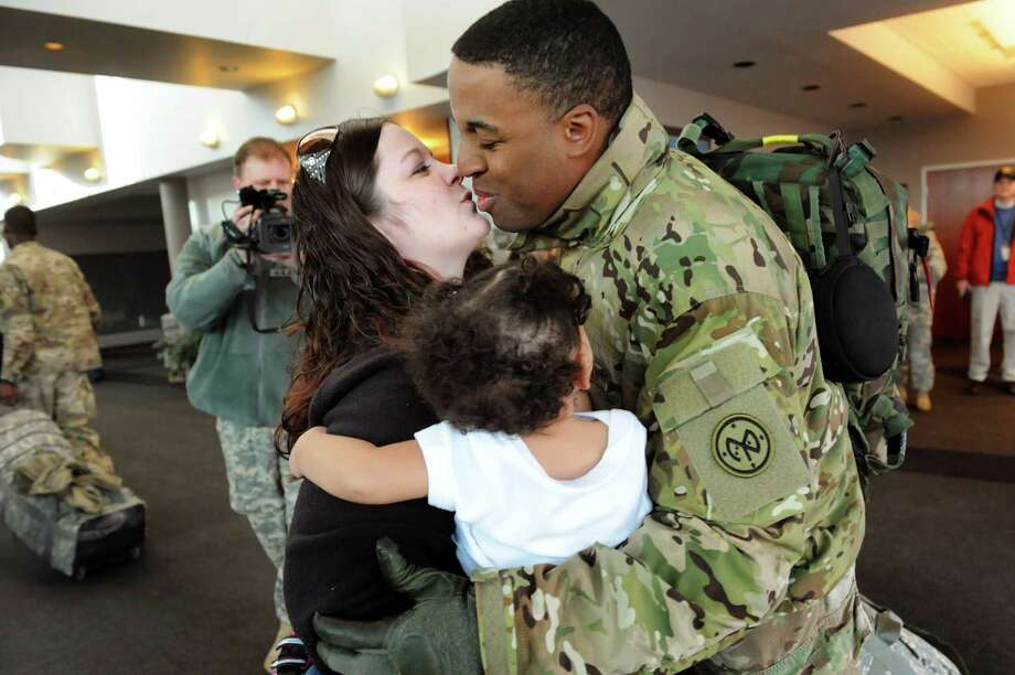 Sgt. 1st Class Antoine Juste of Chittenango, right, reunites with his wife, Mary, and twin daughters Danika and McKinley, 14 months, on Tuesday, Jan. 8, 2013, at Albany International Airport in Colonie, N.Y. Troops from the 27th Infantry Brigade reunite with family and friends following their deployment to Kuwait in support of Operation Enduring Freedom. (Cindy Schultz / Times Union) Photo: Cindy Schultz / 00020696A