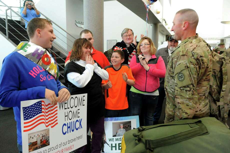 Sgt. 1st Class Charles Peuser, right, of St. Johnsville reunites with his girlfriend, Kelly Gray, second from left, and family on Tuesday, Jan. 8, 2013, at Albany International Airport in Colonie, N.Y. Troops from the 27th Infantry Brigade reunite with family and friends following their deployment to Kuwait in support of Operation Enduring Freedom. (Cindy Schultz / Times Union) Photo: Cindy Schultz / 00020696A