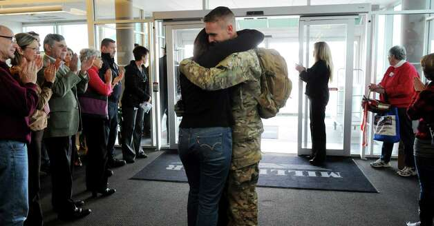 A soldier reunites with a loved one on Tuesday, Jan. 8, 2013, at Albany International Airport in Colonie, N.Y. Troops from the 27th Infantry Brigade reunite with family and friends following their deployment to Kuwait in support of Operation Enduring Freedom. (Cindy Schultz / Times Union) Photo: Cindy Schultz / 00020696A