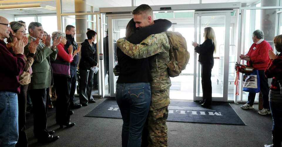A soldier reunites with a loved one on Tuesday, Jan. 8, 2013, at Albany International Airport in Col