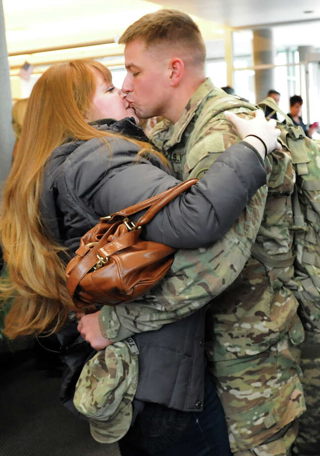 Capt. Nicholas Tommaso of Carle Place, Nassau County, right, embraces his girlfriend, Brittany Carr, on Tuesday, Jan. 8, 2013, at Albany International Airport in Colonie, N.Y. Troops from the 27th Infantry Brigade reunite with family and friends following their deployment to Kuwait in support of Operation Enduring Freedom. (Cindy Schultz / Times Union) Photo: Cindy Schultz / 00020696A
