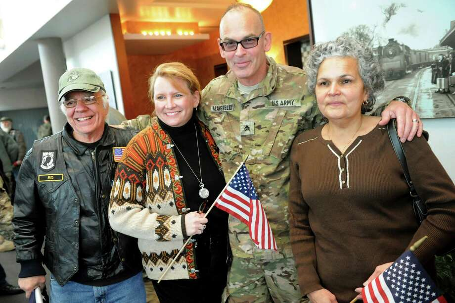 Sgt. Bill Mansfield of Spring Valley, center, poses with friends when he arrives home on Tuesday, Jan. 8, 2013, at Albany International Airport in Colonie, N.Y. From left are Ed Steedle, Claudia Cooley and Gilda Klug. Troops from the 27th Infantry Brigade reunite with family and friends following their deployment to Kuwait in support of Operation Enduring Freedom. (Cindy Schultz / Times Union) Photo: Cindy Schultz / 00020696A