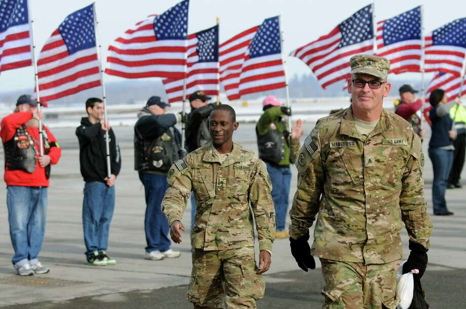 Sgt. Bill Mansfield of Spring Valley, right, arrives home on Tuesday, Jan. 8, 2013, at Albany International Airport in Colonie, N.Y. Troops from the 27th Infantry Brigade reunite with family and friends following their deployment to Kuwait in support of Operation Enduring Freedom. (Cindy Schultz / Times Union) Photo: Cindy Schultz / 00020696A