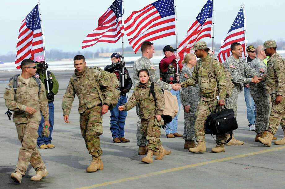 Troops arrive home on Tuesday, Jan. 8, 2013, at Albany International Airport in Colonie, N.Y. Troops from the 27th Infantry Brigade reunite with family and friends following their deployment to Kuwait in support of Operation Enduring Freedom. (Cindy Schultz / Times Union) Photo: Cindy Schultz / 00020696A