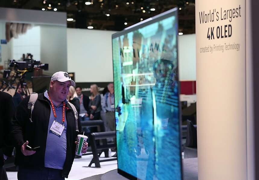 An attendee looks at a display of the Panasonic 4K OLED 56