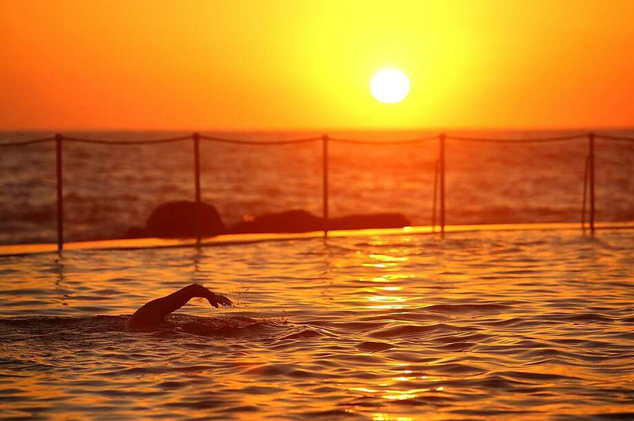 It's so hot in Sydney that even the swimmers are up early doing laps before the sun bakes Bronte Beach. The city was expecting record high temperatures. Photo: Marianna Massey, Getty Images