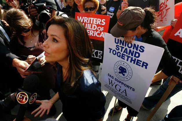 Actress Eva Longoria (L) speaks with members of the media during a break in filming while comedian and actress Wanda Sykes (C) and actress Julia Louis-Dreyfus (R) hold picket signs and listen as Hollywood writers picket outside the set of Desperate Housewives on the second day of the strike following a break-down in talks between the Writers Guild of America (WGA) and the Alliance of Motion Picture and Television Producers November 6, 2007 in Los Angeles, California. Julia Louis-Dreyfus, who is a Screen Actors Guild (SAG) member, is picketing with the writers of her current show, The New Adventures Of Old Christine which has ended production as a result of the strike. Striking are 12,000 WGA union members for the first time since 1988 when a 22-week walkout cost the entertainment industry an estimated $500 million. The industry cost of this strike could reach one billion. Photo: David McNew, Getty Images / Getty Images North America
